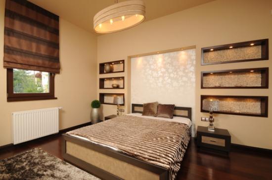 Mooie gipsplaten nissen met decoratieve verlichting aan de muur aan het hoofdeinde van het bed in de slaapkamer