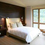 Houten lambrisering aan het hoofdeinde van het bed in de slaapkamer