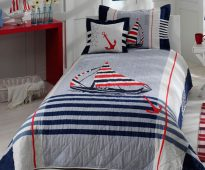Couvre-lit de bébé sur le lit pour les garçons dans le style marin