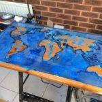 Een tafel met een gloeiende kaart van epoxyhars in uw handen