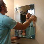Nous accrochons un miroir dans la photo de la salle de bain
