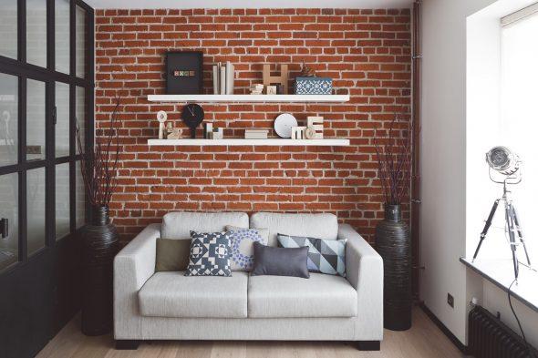 Hyllyt sohvan yläpuolella pienessä huoneessa