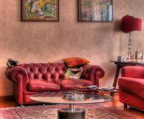 Canapé rouge contre un mur en terre cuite