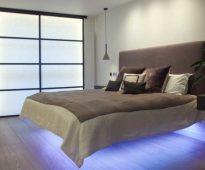 Un lit avec un dos mou et des lumières en dessous