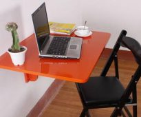 Table pliante orange pour travailler devant un ordinateur
