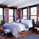 Chambre avec de grandes fenêtres avec un lit fait à la main