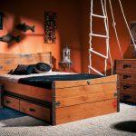 Les tiroirs en bois sous le lit font écho au meuble et à la commode