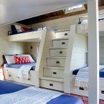 Des boîtes sous les lits et dans les marches pour une chambre compacte pour plusieurs enfants