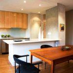 Cuisine en bois avec des comptoirs en pierre et des placards jusqu'au plafond