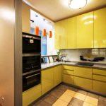 Cuisine jaune avec grandes armoires murales