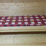 Lit en bois simple dans une chambre en bois faites-le vous-même