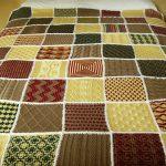 Grand plaid sur un lit de divers motifs tricotés