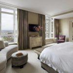Belle chambre aux couleurs apaisantes avec beaucoup de meubles.