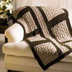 Beau couvre-lit à carreaux avec des tresses sur le canapé