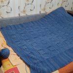 Une grande couverture tricotée bleue ira bien sur un lit ou un canapé