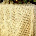 Plaid tricoté jaune avec des glands