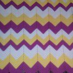 Un plaid blanc-jaune-lilas avec un motif en zigzag décorera votre intérieur.