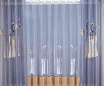Délicat rideau bleu avec des fleurs