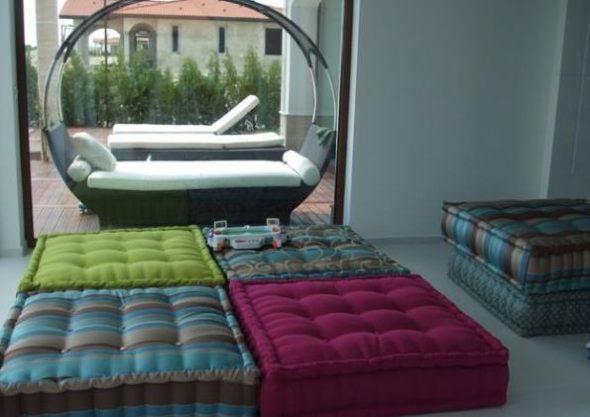 Grote woonkamer met kussens in plaats van gestoffeerde meubels.