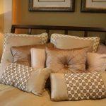 Decoratieve kussens op het bed van drie soorten materialen in verschillende combinaties