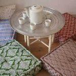Vierkante kussens op de grond voor een comfortabel theekransje