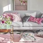 Multi-gekleurde kussens verfrissen het interieur van de grijze kamer