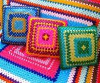 Plaid et oreillers sur le canapé des fils colorés en forme de carré
